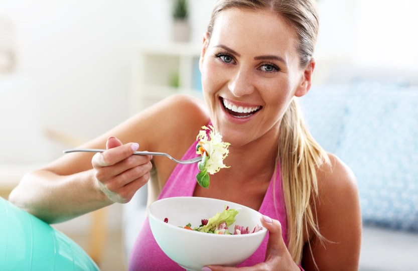 Intermittent fasting Young woman eating healthy salad after workout